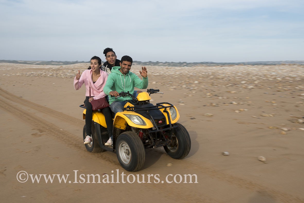 Marokko, Sidi Kawki, 20150303.Toeristen zitten en rijden met een chauffeur op een quad langs de atalantische kust Marokkaanse gids. Turists and their driver, driving at a quad along the coast. Model released. Naamsvermelding verplicht; Foto ; Sabine Joosten/Hollandse Hoogte