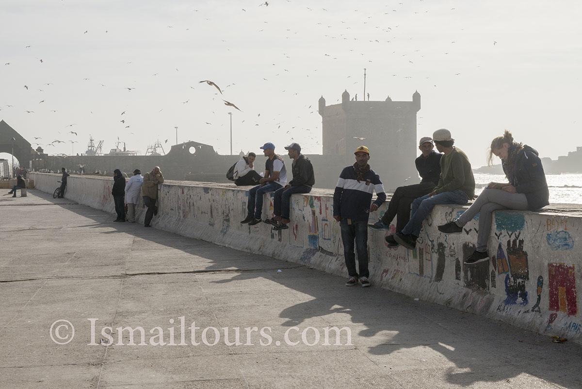 Marokko, Essaouira 20150304. Inwoners van de stad hangen tegen een muur,tje aan de zee, ontmoetingsplek. Meeting each other at the seaside. Naamsvermelding verplicht; Foto ; Sabine Joosten/Hollandse Hoogte