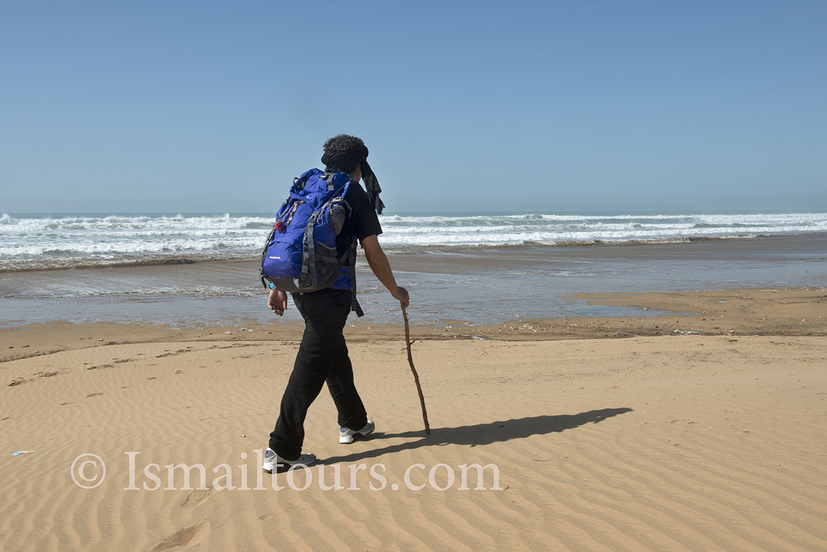 Marokko, Sidi Kaouki, 20150305. Atlantische kust,. Marokkaanse gids loopt langs de kust met een rugzak. Guide walking along the coast with a backpack. Model released. Naamsvermelding verplicht; Foto ; Sabine Joosten/Hollandse Hoogte